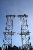 Big double electricity pylon in the forest — Stock Photo