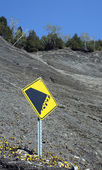 Falling rocks sign on the mountain slope — Stock Photo
