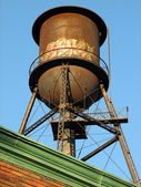 Old water tower on the roof — Stock Photo