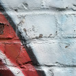 Stock Photo: Graffiti on a peeling brick wall