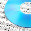 Stock Photo: Blue CD or DVD on sheet music