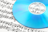 Blue CD or DVD on sheet music — Stock Photo