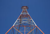 Red triangular power tower in the blue sky — Stock Photo