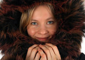Smiling young woman with a fur hood — Stock Photo