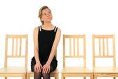 Jovencita sentada en una silla y esperando — Foto de Stock