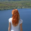Red-haired girl looking over blue lake — Stock Photo