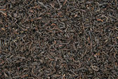 Black tea leaves background — Stock Photo