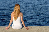 Longhaired girl sitting by the sea — Stock Photo
