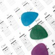Colorful guitar picks on a chords chart - Stock Photo