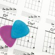 Guitar picks on a chords chart — Stock Photo