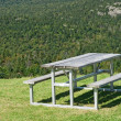 Picnic table with view over mountain forest — Stock Photo