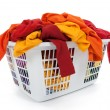 Bright clothes in laundry basket. Red, orange, yellow. — Stock Photo