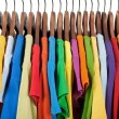 Variety of multicolored clothes on wooden hangers — Stock Photo