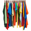 Variety of multicolored shirts on wooden hangers - Стоковая фотография