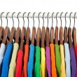 Multicolored clothes on wooden hangers — Stock Photo