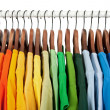 Rainbow colors, clothes on wooden hangers — Stock Photo