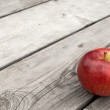 Red apple on old wooden table — Stock Photo #22198103