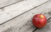 Red apple on old wooden table — Stock Photo