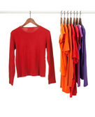 Red and purple shirts on wooden hangers — Stock Photo