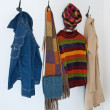 Постер, плакат: Colorful clothing on coat hooks