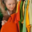 Curious girl looking out of the clothes rack — Stock Photo #22227117