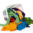 Bright clothes falling out of a laundry basket - Stock Photo