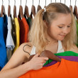 Girl choosing clothes in a store — Stock Photo