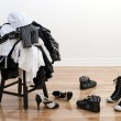 Постер, плакат: Heap of clothing on a stool and disordered shoes
