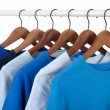 Casual shirts on hangers, different tones of blue — Stock Photo