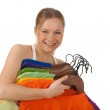 Charming young woman holding colourful clothes — Stock Photo