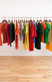 Variety of multicolored clothes on a rod — Stock Photo