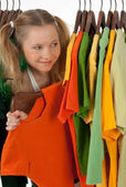 Curious girl looking out of the clothes rack — Stock Photo