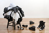 Heap of clothing on a stool and disordered shoes — Stock Photo