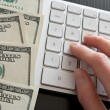 Stock Photo: Counting money on computer calculator