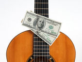 Classical guitar and money — Stock Photo