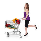 Smiling girl with shopping cart buying colorful clothing — Stock Photo