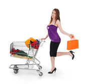 Smiling girl with shopping cart and orange bag — Stock Photo