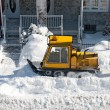 Yellow snowplough removing snow in the city - Stock Photo