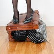 Постер, плакат: Woman in high heel shoes standing on overfilled suitcase