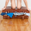 Woman trying to close overfilled suitcase — Stock Photo #22338175