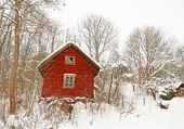 Very old red wooden house in a snowy forest — Stock Photo