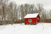 Traditional Swedish red wooden house in snow — Stock Photo