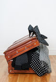 Polka dot clothing in a vintage leather suitcase — Stock Photo