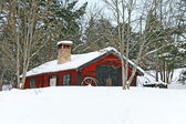 Rustic red wooden barn in snow — Stock Photo