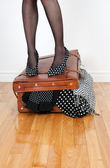 Woman in high heel shoes standing on overfilled suitcase — Stock Photo