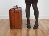 Woman in brown stockings standing near vintage suitcase — Foto de Stock