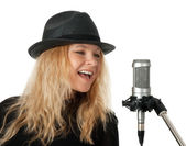 Singer in black hat singing with the microphone — Stock Photo