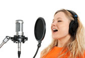 Girl in headphones singing with studio microphone — Stock Photo