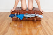 Woman trying to close overfilled suitcase — Stockfoto