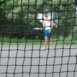 Tennis player seen through the net — Stock Photo